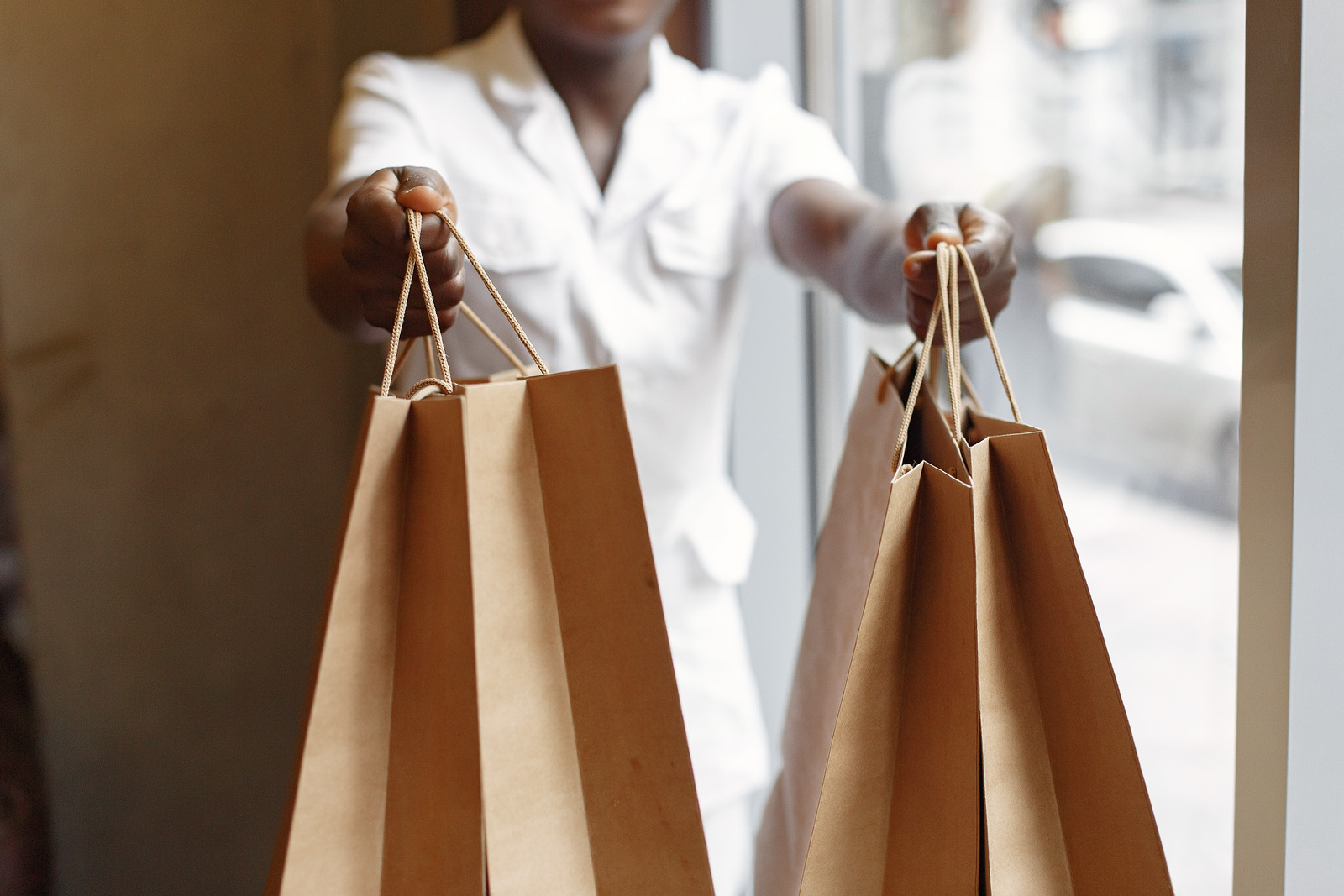 Sales clerk handing bags from an impulsive shopping trip
