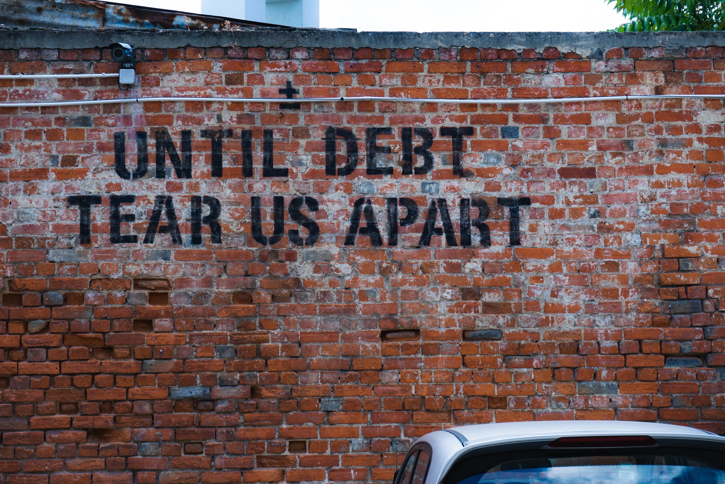"Wall with script ""until debt tear us apart"""